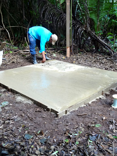 Marcelino Pop smooths the cement slab for the hot/cold shower in the research compound.